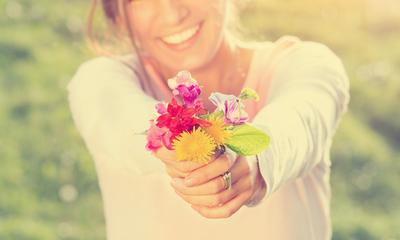 Smiling girl holding flowers.