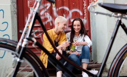 Two girlfriends drinking a  soft drink. A bicycle is in the foreground.